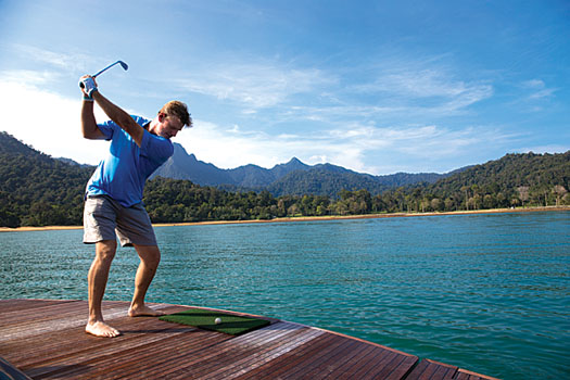 Ernie Els tees off from the back of a yacht towards the Els Club Teluk Datai