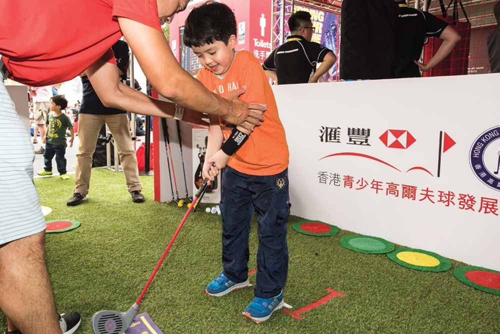 A young rugby fan tries golf for the first time at the Hong Kong Golf Association's Junior Golf Challenge in the HSBC Sevens Village