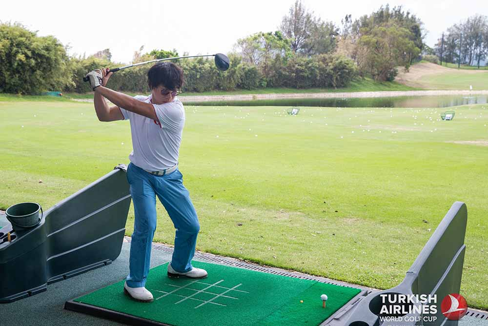 Louie Chan, our Managing Editor, warms up at the driving range