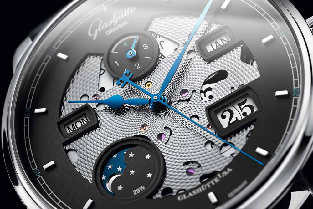 The matte grey dial has been partially opened in the centre and around the indications to reveal the main plate of the perpetual calendar module