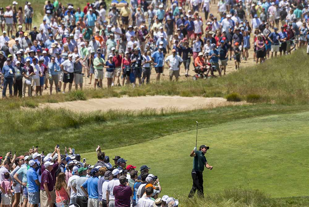 Phil Mickelson watches a shot from the rough on the ninth hole